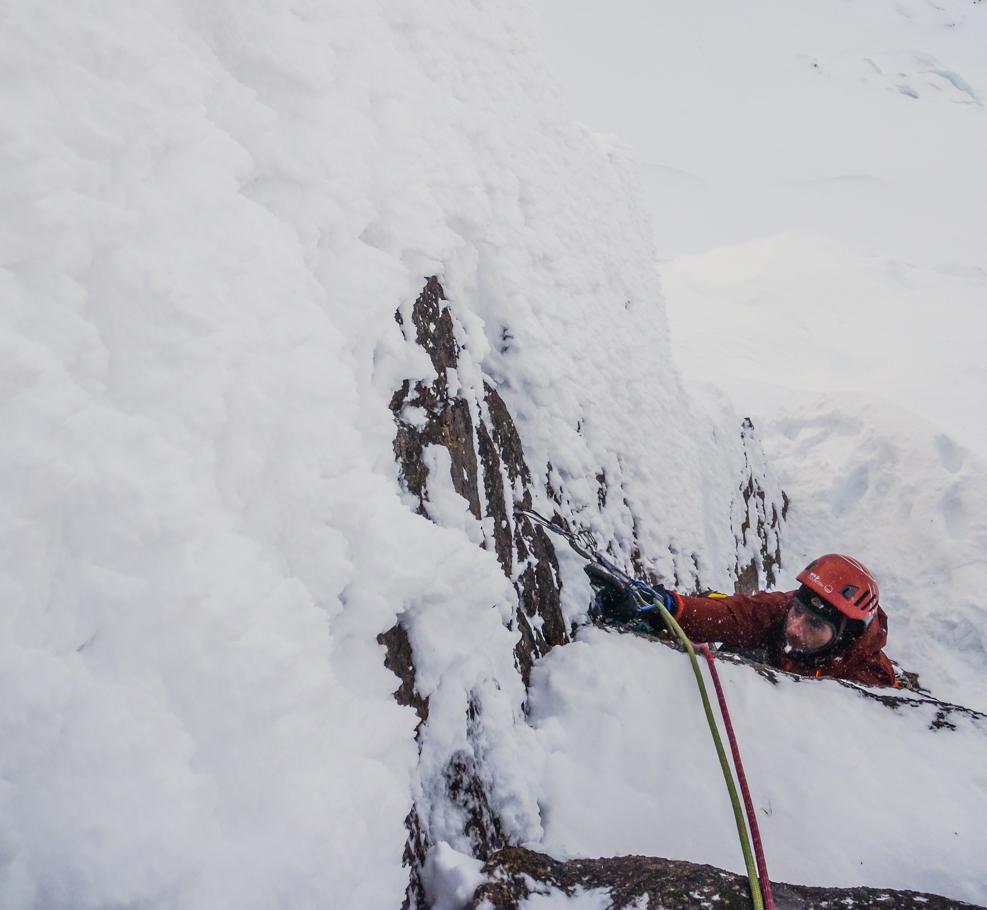 Trying hard on the crux corner and nearing the desperate mantle on to the powder covered slab above. Photo credit: Andy Inglis.
