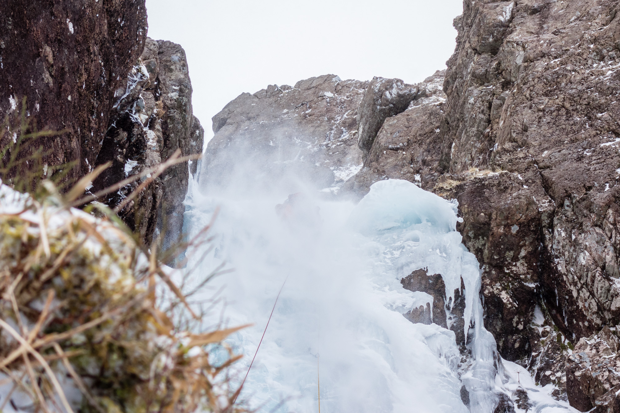 From the shelter of the belay Ric captures a refreshing spindrift shower, which felt like lasted forever! Photo credit: Ric Hines